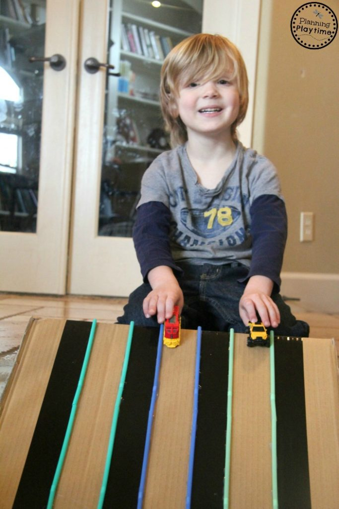 DIY Cardboard Car Track for kids. Made from an old box and drinking straws. Ramp it on the stairs for a fast track.