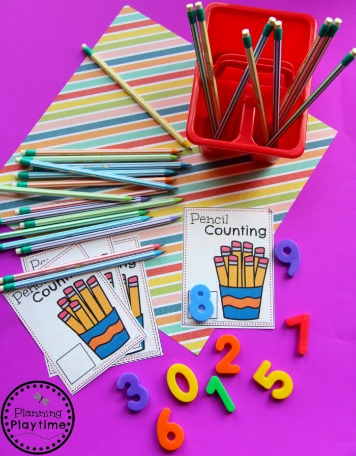Pencil counting cards next to plastic numbers and a bin with pencils to count.