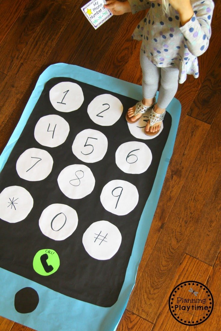 Giant cell phone made from paper on floor. Child stepping on number buttons to make phone number.
