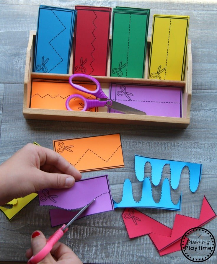 tray with colored paper cutting practice strips and a child cutting with scissors.