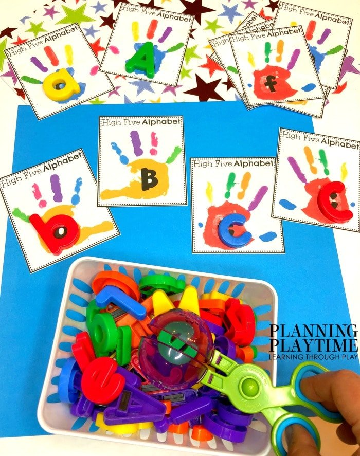 Colorful handprint cards with letters on them.