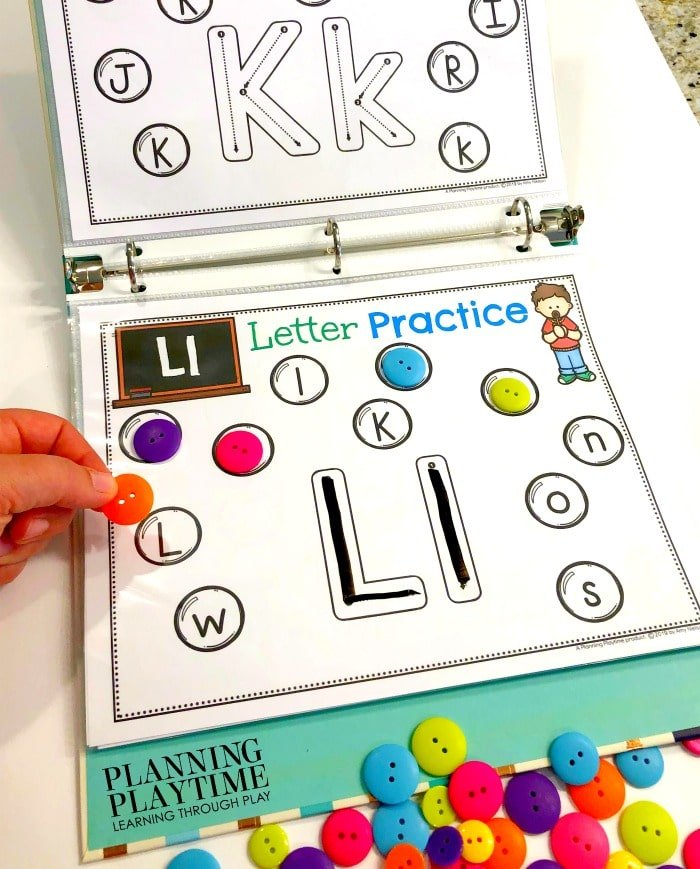 Alphabet Printables in a binder with buttons covering the matching letters