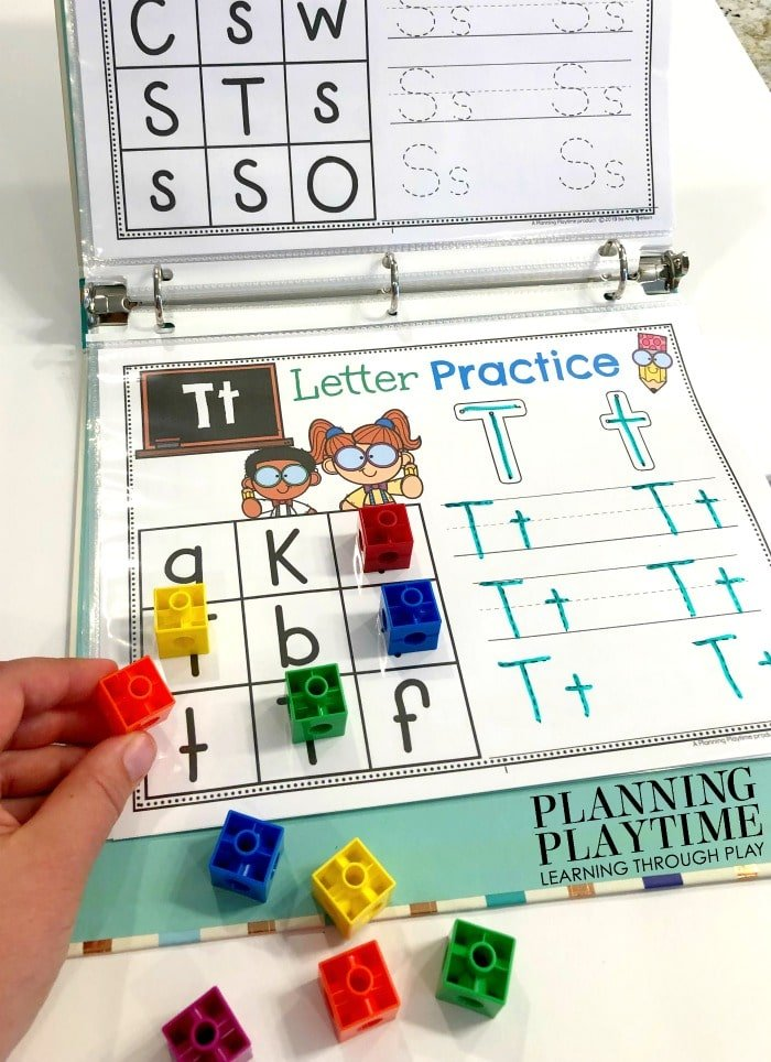 Alphabet printable in a binder with dry erase marker to trace and snap cubes covering the matching letters
